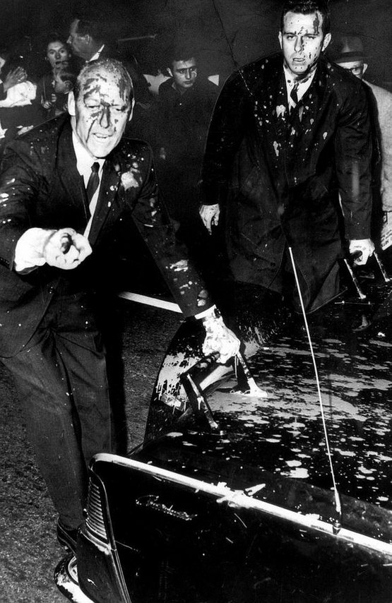 1966_us_president_lyndon_johnson_s_bodyguard_rufus_youngblood_covered_with_paint_and_pointing_out_the_anti-vietnam_protesters_who_threw_it_melbourne_australia.jpg
