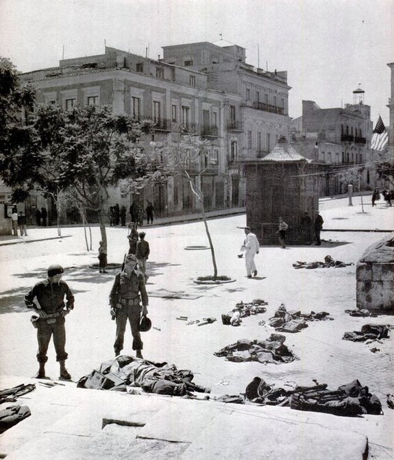 1943_aftermath_of_the_battle_of_gela_sicily_12_july_1943_american_soldiers_civilians_and_casualties_in_the_cathedral_square.jpg