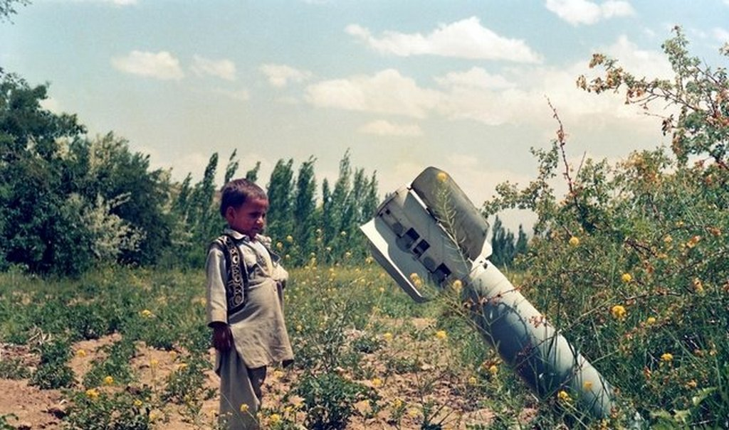 1989_a_young_afghan_boy_observing_an_unexploded_bomb_dropped_by_russian_forces_in_the_soviet_afghan_war.jpg