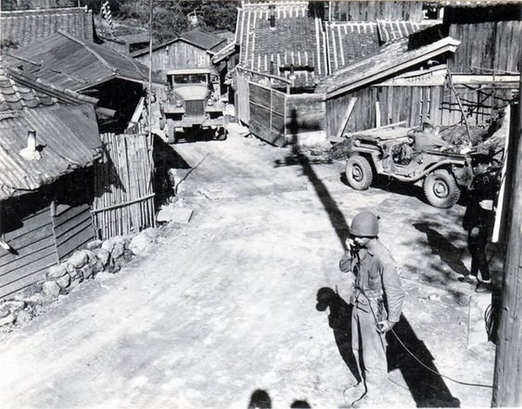 1945_szeptember_u_s_soldier_taking_a_phone_call_utility_pole_at_the_side_of_a_narrow_one-lane_road_tomachi_and_kamitomachi_nagasaki_japan.jpg