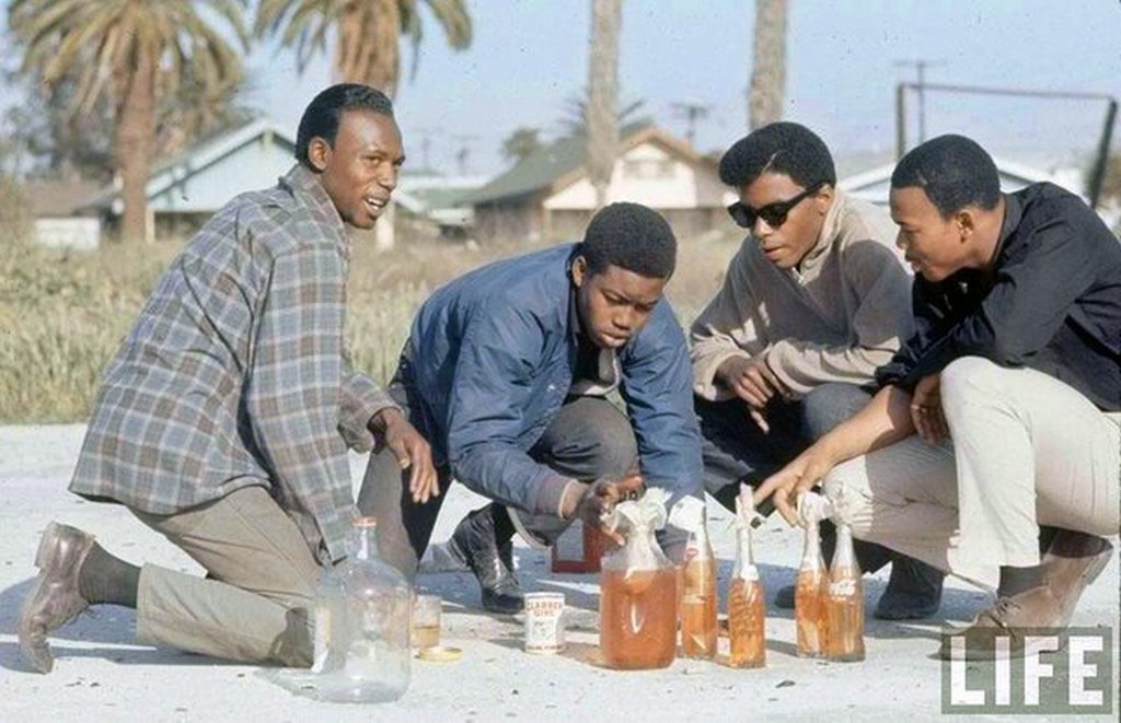 1966_gang_members_pour_motor_oil_into_glass_bottles_to_make_molotov_cocktails_in_the_watts_neighborhood_los_angeles_california.jpg