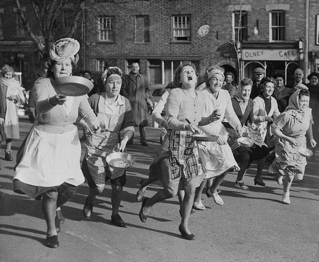1951_british_housewives_toss_pancakes_in_skillets_as_they_run_through_the_streets_of_olney_england.jpg