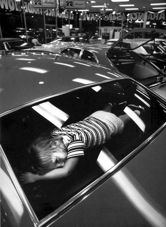 1971_car_showroom_atlanta_georgia_usa_while_her_parents_slammed_car_doors_and_tested_radios_this_girl_tried_out_the_ledge_behind_the_back_seat.jpg