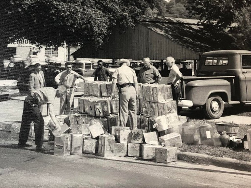 1959_authorities_pouring_confiscated_whiskey_down_a_street_drain_in_tallahassee_florida.jpg
