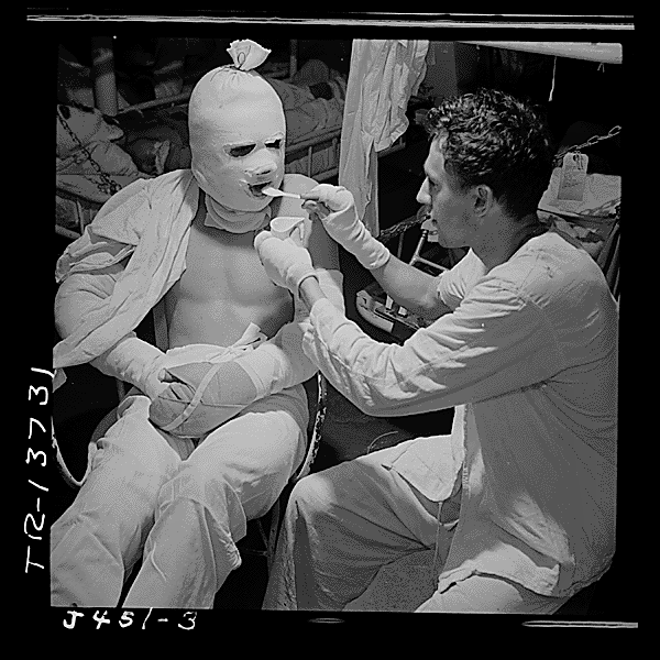 1945_a_sailor_who_was_burned_in_a_kamikaze_attack_being_fed_aboard_the_uss_solace.png
