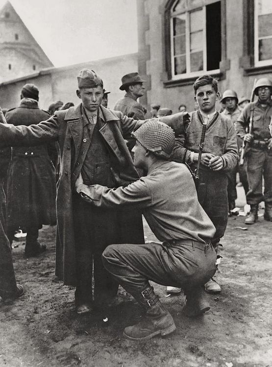 1945_a_teenager_of_the_volkssturm_is_searched_by_a_us_soldier.jpg
