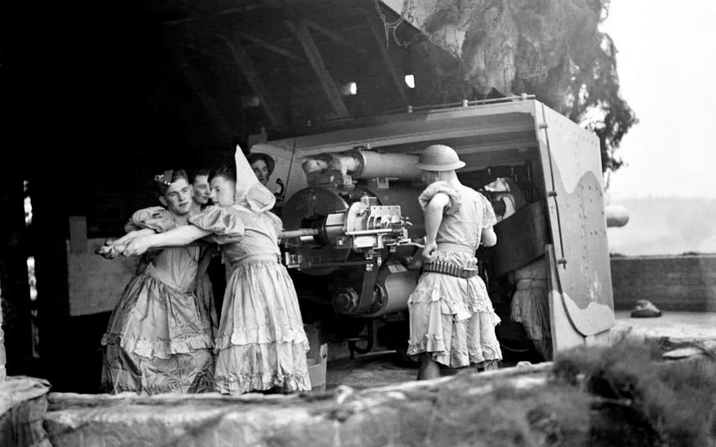 1940_soldiers_who_were_interrupted_during_rehearsals_for_a_drag_show_by_an_air_raid_manning_anti-aircraft_guns_at_the_royal_artillery_coastal_defence_battery_at_shornemead_fort_kent_england.jpg
