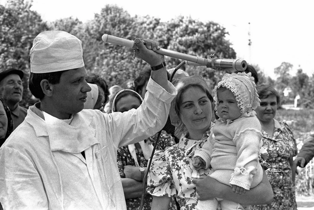 1986_a_soviet_technician_checks_the_toddler_katya_litvinova_during_a_radiation_inspection_of_residents_in_the_village_of_kopylovo_near_kiev_on_may_9.png