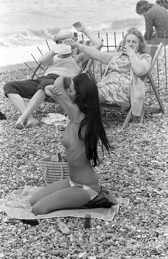 1974_wife_shields_her_husband_s_eyes_from_a_young_woman_taking_her_top_off_on_the_beach_france.jpg