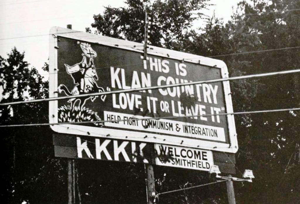1977_kkk_sign_with_tag_love_it_or_leave_it_in_smithfield_nc.png
