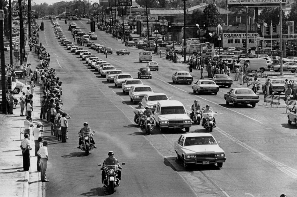 1977_augusztus_19_white_vehicles_follow_the_hearse_carrying_the_body_of_rock_and_roll_musician_elvis_presley_along_elvis_presley_boulevard_on_the_way_to_forest_hills_cemetery_in_memphis_tenn.jpeg