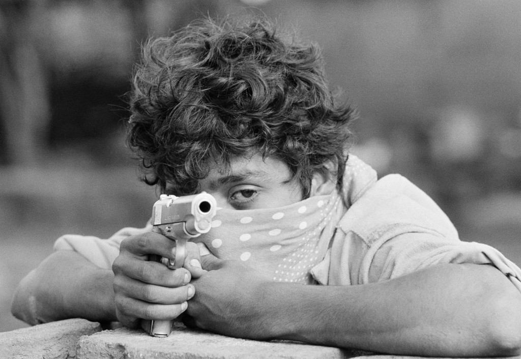 1979_sandinista_guerrilla_takes_aim_with_his_45_pistol_as_he_stands_waiting_to_do_combat_with_the_nicaraguan_national_guard_in_managua.jpeg