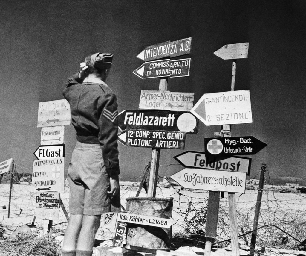 1942_oktober_a_british_soldier_following_up_the_tanks_is_somewhat_perplexed_by_the_multiplicity_of_german_and_italian_signs_at_the_entrance_to_mersa_matruh.jpeg