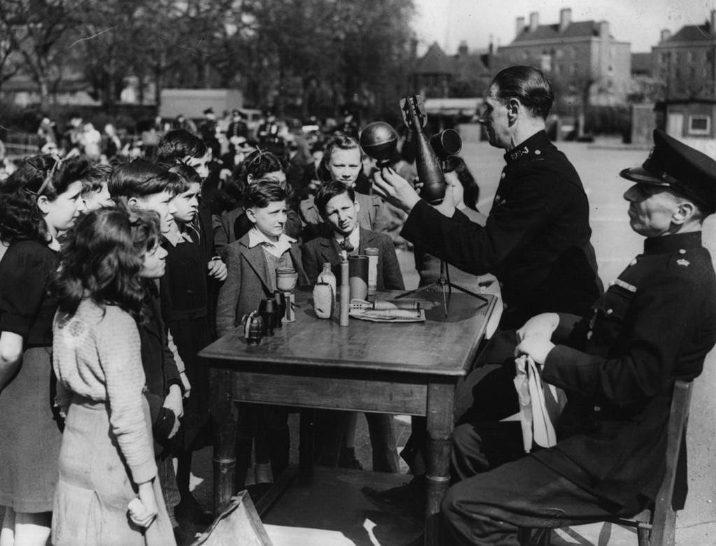 1943_children_in_hackney_uk_are_advised_on_road_safety_and_the_dangers_of_picking_up_strange_objects_by_police_officers.jpeg
