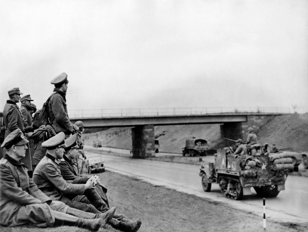 1945_aprilis_18_german_officers_sitting_on_the_side_of_the_road_watching_tanks_of_the_allies_using_the_autostrades_motorways_built_by_hitler_for_his_troops.jpeg
