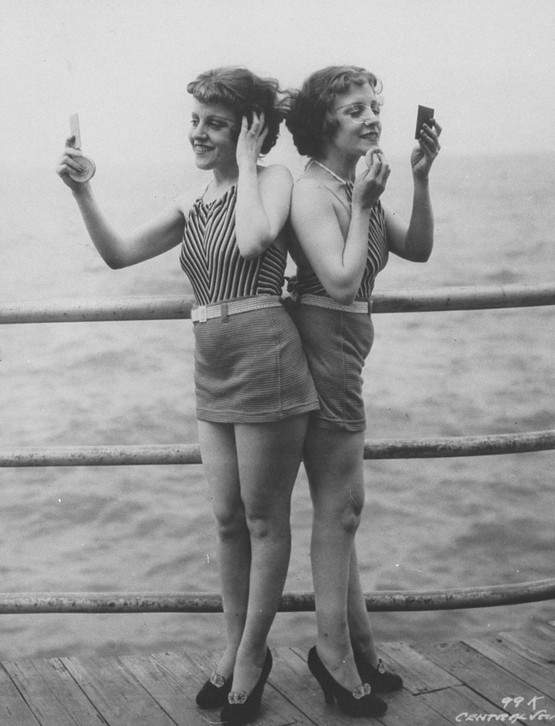 1946_siamese_twins_violet_daisy_hilton_standing_back-to-back_looking_in_hand_mirrors_and_powdering_faces_on_pier_at_atlantic_city.jpeg