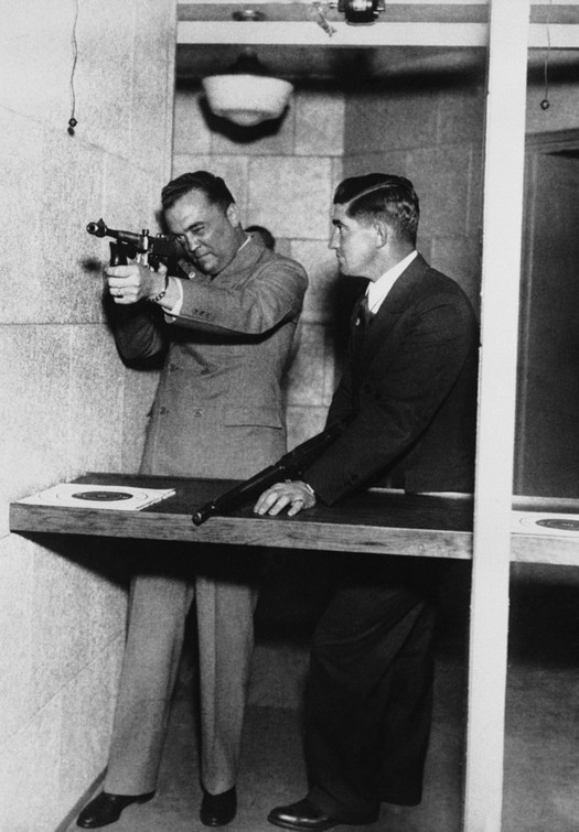 1935_j_edgar_hoover_head_of_the_fbi_demonstrates_the_use_of_a_machine_gun_at_the_department_of_justice_to_mickey_cochrane_right_manager_of_the_detroit_tigers_in_washington.jpeg