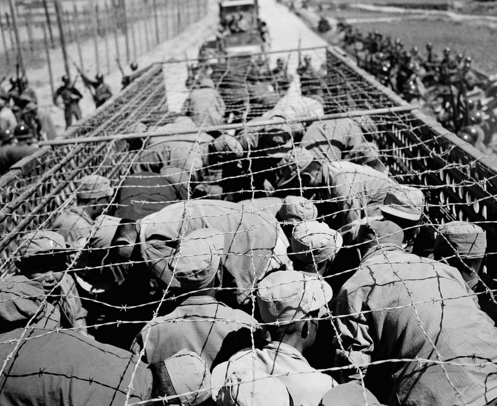 1952_junius_north_korean_prisoners_huddle_under_barbed_wire_as_they_are_transported_from_one_compound_to_another_on_koje_island.jpeg