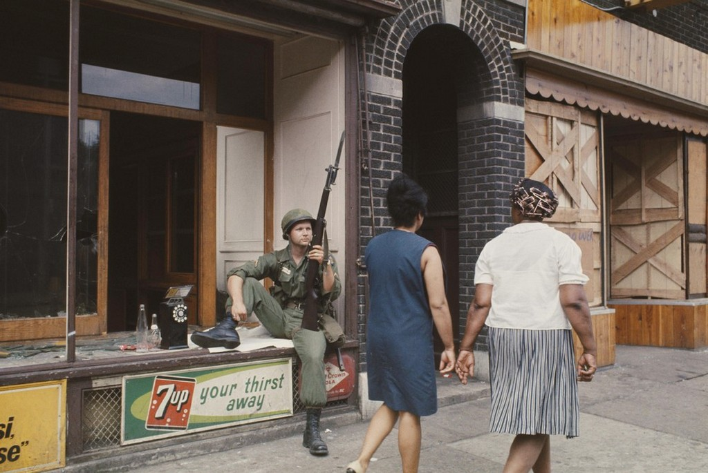 1967_julius_a_national_guardsman_armed_with_a_rifle_and_bayonet_rests_in_the_window_of_a_wrecked_shop_front_in_a_shopping_street_in_detroit_following_three_days_and_nights_of_rioting.jpeg