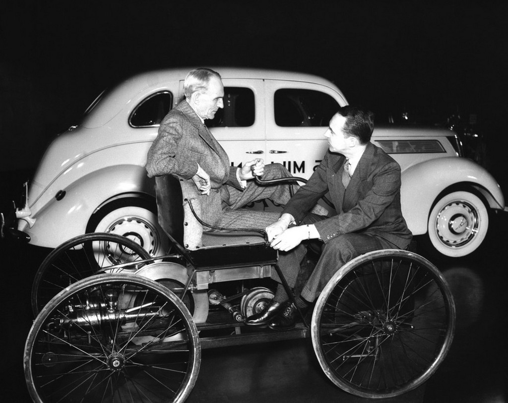 1939_henry_ford_and_his_son_edsel_ford_here_they_are_sitting_on_the_elder_ford_s_first_car_with_the_25-millionth_in_the_background.jpeg