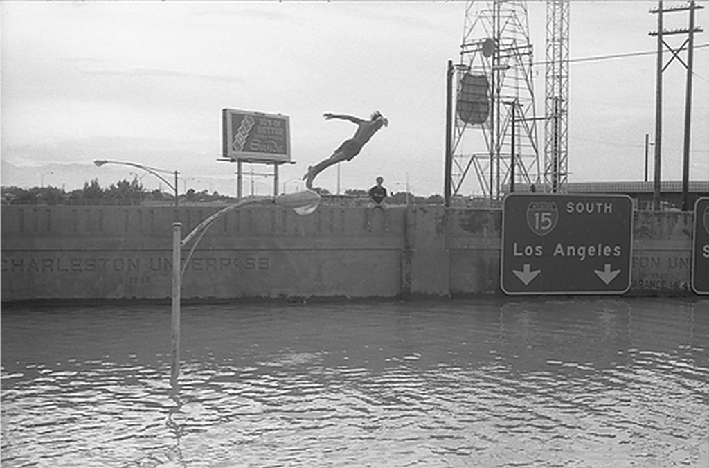 1950_teen_jumping_into_flood_waters_from_a_light_pole_in_las_vegas.png