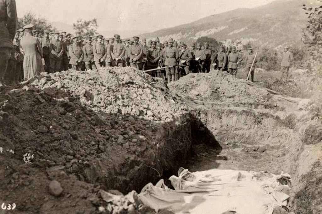 1915_austro_hungarian_soliders_stand_in_front_of_a_mass_grave_on_the_eastern_front.jpeg