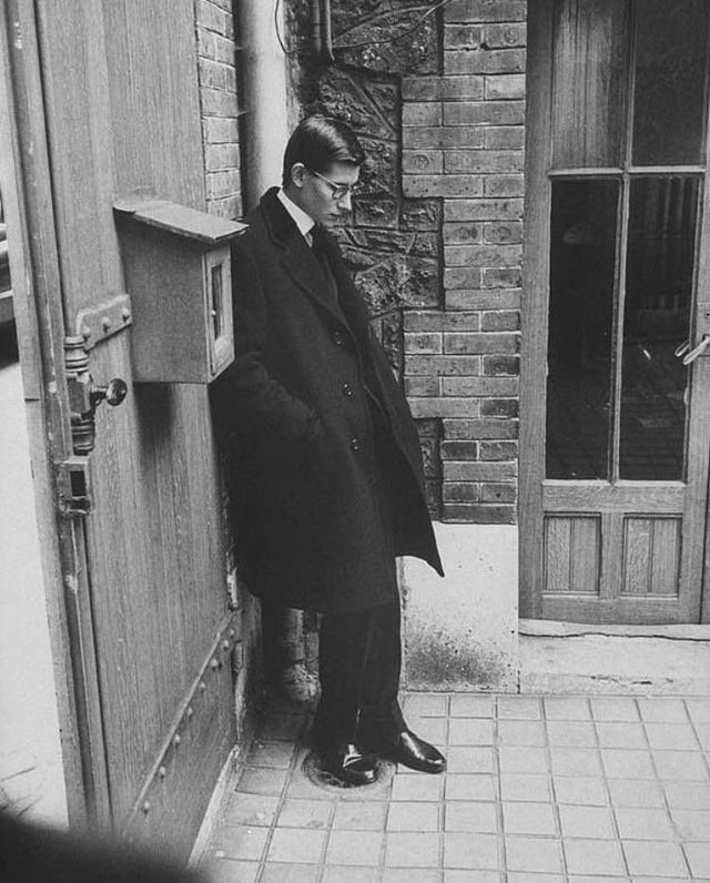 1957_yves_saint_laurent_standing_alone_after_attending_dior_s_funeral_paris.jpg