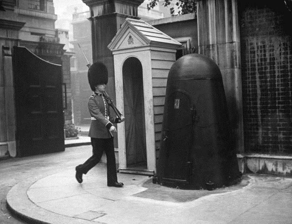 1940_a_queen_s_guard_with_an_individual_air_raid_shelter_next_to_sentry_box_during_the_blitz_london.jpg