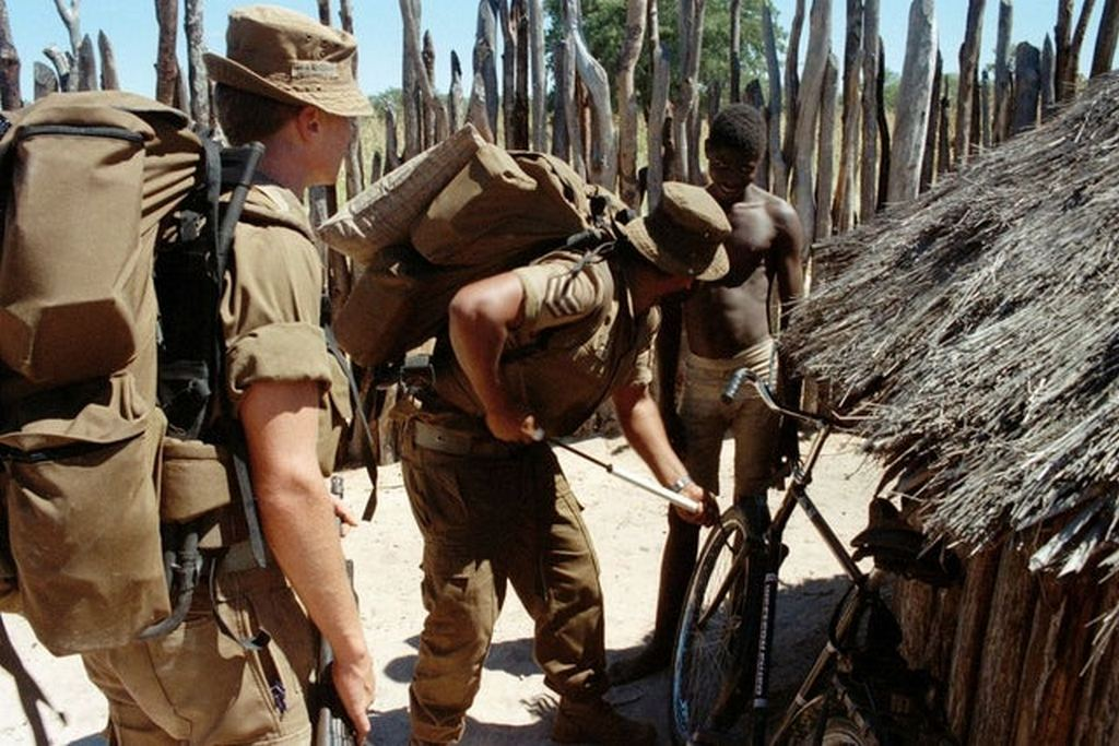 1988_a_south_african_soldier_on_patrol_in_namibia_helps_a_local_pump_up_the_tires_on_his_bicycle.jpg