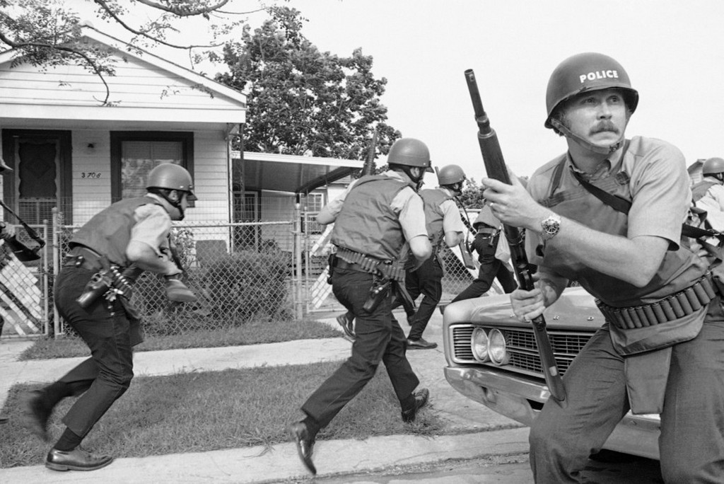 1970_new_orleans_police_officers_try_to_keep_their_heads_down_as_they_move_in_on_a_black_panther_headquarters_during_an_exchange_of_gunfire.jpeg