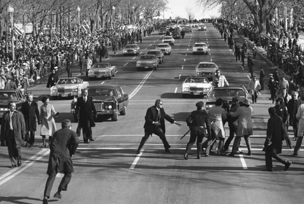 1977_president_jimmy_carter_and_first_lady_rosalynn_watch_left_as_police_and_secret_service_officials_remove_a_spectator_right_who_burst_into_the_inaugural_parade_washington.jpg