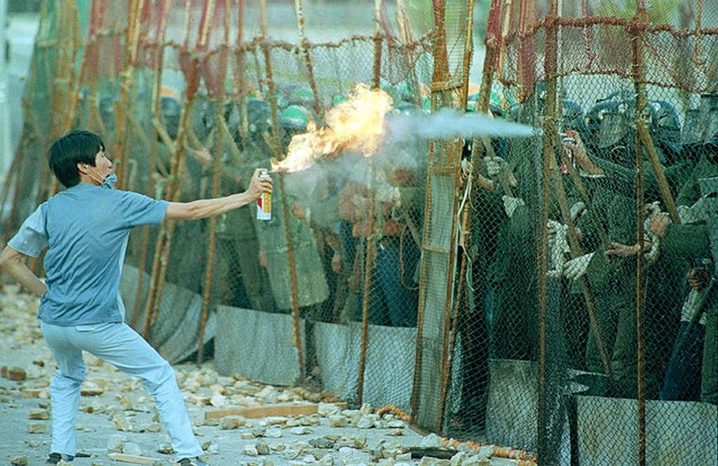 1987_a_south_korean_student_sprays_a_flaming_aerosol_can_as_riot_police_respond_with_a_fire_extinguisher_during_an_anti-government_demonstration_at_yonsei_university_in_seoul_korea.jpg