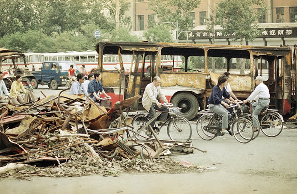 1989_bicyclists_peddle_through_the_ruins_of_the_last_weeks_battle_between_the_peoples_liberation_army_and_students_demonstrating_for_democracy_in_tiananmen_square.jpg