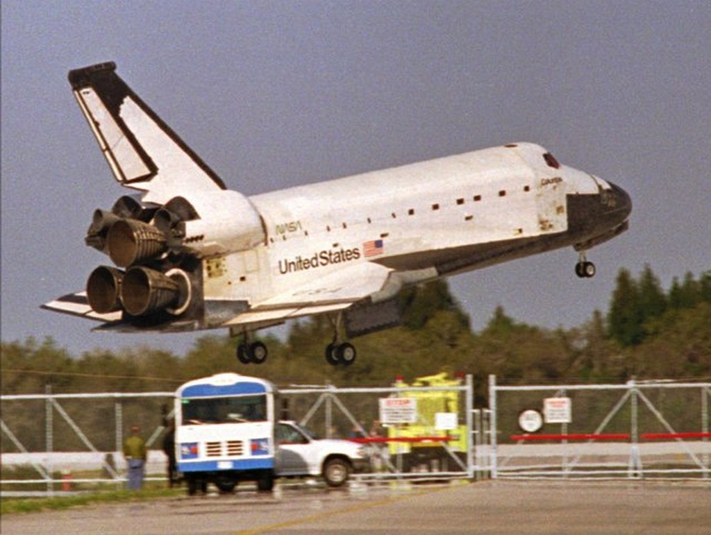 1996_the_space_shuttle_columbia_glides_by_rescue_vehicles_before_touching_down_on_kennedy_space_center_s_runway_33_early_saturday_morning_march_9_1996_ending_a_16-day_mission.jpg