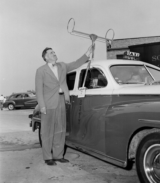 1948_george_fyler_television_engineer_adjusts_the_antenna_he_designed_for_the_first_installation_of_a_television_set_in_a_taxicab_shown_in_chicago.jpeg
