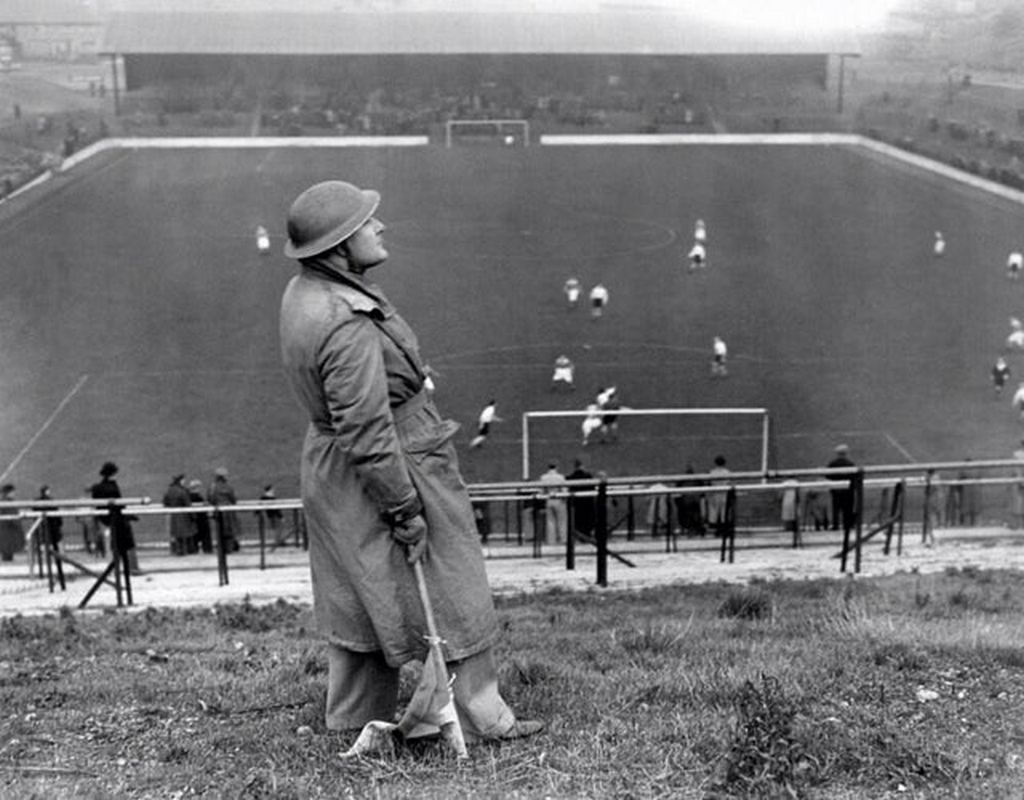 1940_a_spotter_watches_for_german_air_raids_while_premier_league_s_match_arsenal_vs_carlton_athletic_goes_on.jpg