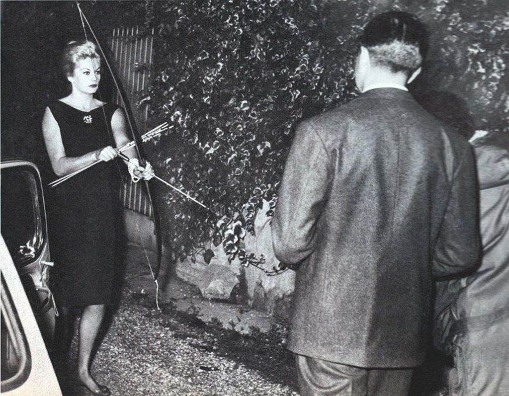 1960_anita_ekberg_brandishes_a_bow_and_arrow_while_confronting_the_paparazzi_photo_by_marcello_geppetti.jpg