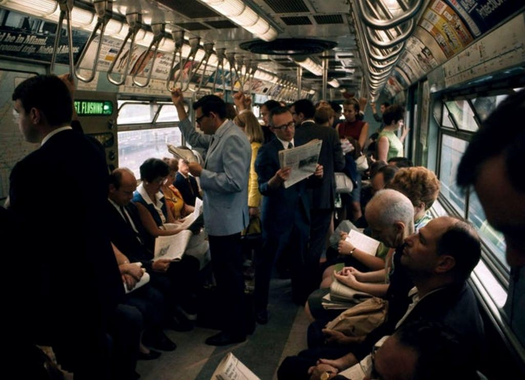 1966_rush_hour_passengers_read_their_newspapers_or_snooze_as_they_ride_the_number_7_train_nyc.jpg