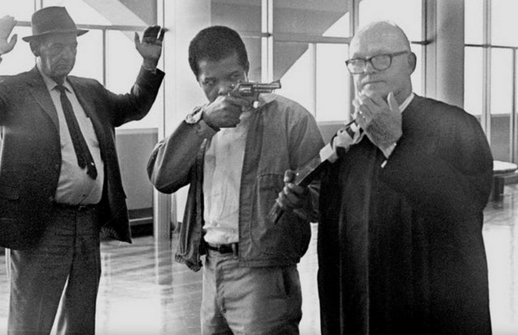 1970_augusztus_7_james_mcclain_points_a_revolver_and_a_sawed-off_shotgun_that_is_taped_to_the_neck_of_judge_harold_j_haley_at_the_marin_county_courthouse.jpg
