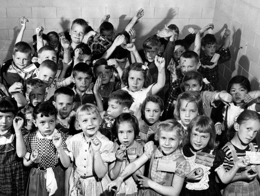1954_children_in_lombard_illinois_eat_cookies_and_show_off_their_arm_stencils_after_being_vaccinated_for_polio.jpg
