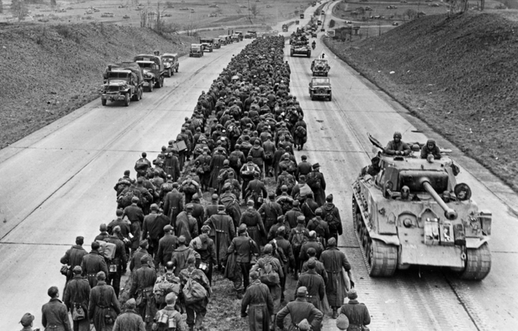 1945_marcius_29_german_pow_s_marching_down_the_autobahn_northwest_of_frankfurt_while_american_troops_advance_to_the_battlefront.png