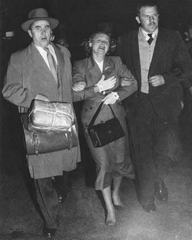 1954_aprilis_evdokia_petrova_at_mascot_airport_sydney_being_escorted_across_the_tarmac_to_a_waiting_plane_by_two_armed_soviet_diplomat.jpeg