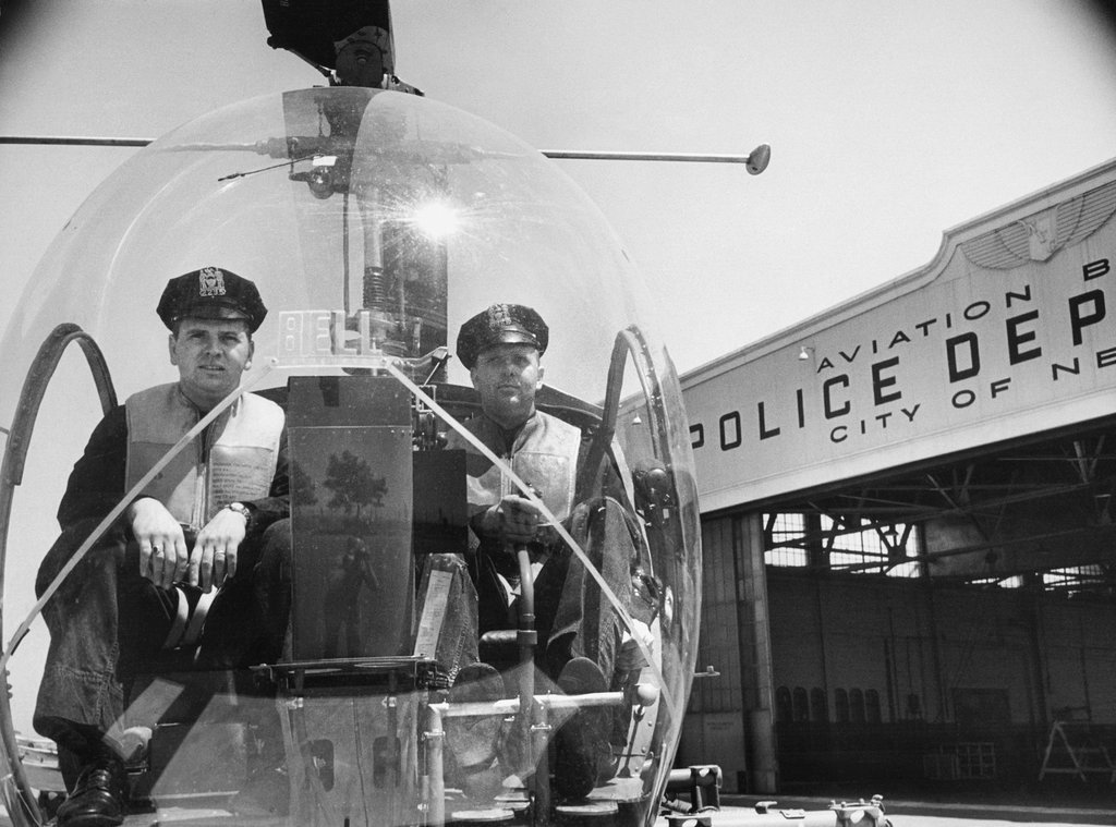 1953_with_the_photographer_sam_falk_visible_on_the_front_of_the_helicopter_s_bubble_shield_two_police_officers_sat_ready_at_floyd_bennett_field_in_brooklyn_to_begin_a_patrol.jpg