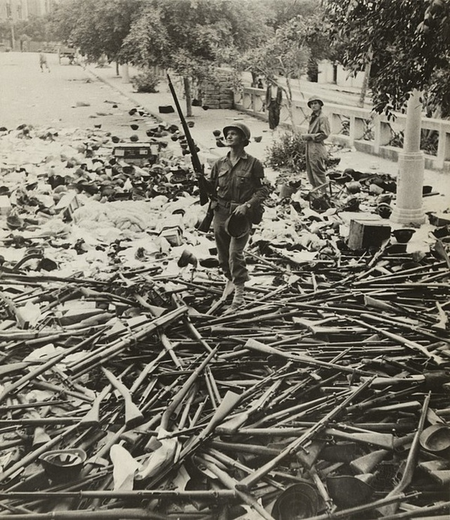 1943_a_u_s_military_police_soldier_standing_on_a_pile_of_italian_rifles_and_helmets_after_the_capture_of_palermo_sicily.jpg