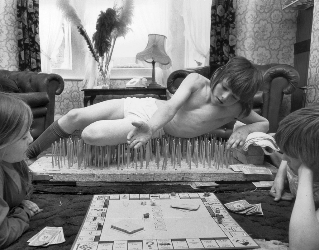 1976_eight-year-old_mark_harman_from_london_enjoying_a_game_of_monopoly_with_his_brother_graham_and_sister_belinda_from_his_bed_of_nails_cr.jpg