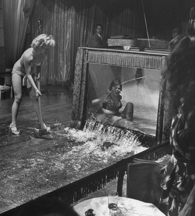 1950_stripper_envy_evangeline_sylvas_angrily_breaking_the_water_tank_being_used_by_fellow_stripper_divena_at_the_casino_royale_club_in_new_orleans.jpg