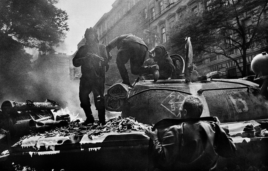 1968_a_russian_tanker_aims_his_akms_rifle_at_a_czech_protester_while_the_rest_of_his_crew_exit_their_t-62_after_molotovs_ignited_the_engine_afire_prague.png