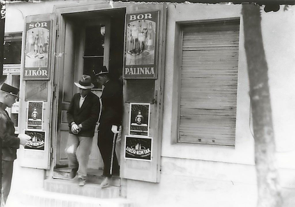 1930-as_evek_rendor_megbilincselt_ferfit_vezet_ki_egy_budapesti_kocsmabol_cr.jpg