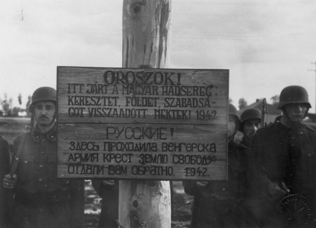 1942_magyar_katonak_egy_tabla_mellett_a_felirat_oroszok_itt_jart_a_magyar_hadsereg_keresztet_foldet_szabadsagot_visszaadott_nektek_cr.jpg