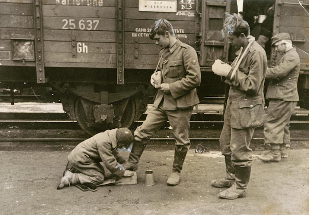 1943_nemet_katonak_csizmajat_tisztito_orosz_fiu_egy_szovjet_palyaudvaron.png